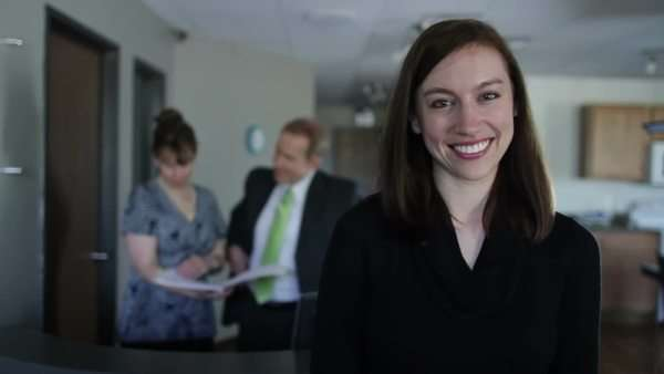 Portrait of a young woman looking at the camera with office action in the background.  Camera mounted on moving jib arm. Royalty-free stock video