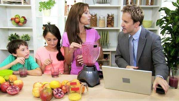 Health conscious Caucasian family home kitchen enjoying nutritious homemade organic fruit juice drink husband working wireless laptop Royalty-free stock video