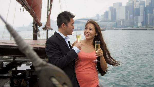 Asian Western couple on corporate hospitality champagne trip on  traditionally designed Chinese junk Hong Kong Harbor