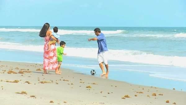 Latin American happy parents playing with young sons by ocean shallows kicking football Royalty-free stock video
