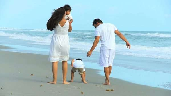Latin American happy parents walking cute young sons ocean shallows outing to beach Royalty-free stock video