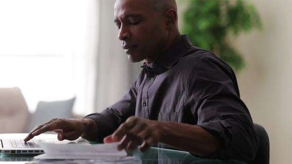 Black man sitting at table using laptop and holding paperwork Royalty-free stock video
