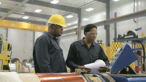 Two black male factory workers discussing paperwork Royalty-free stock video