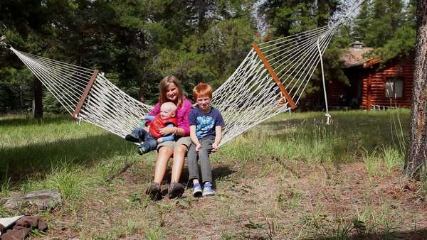 Caucasian boy and girl with baby boy swinging in hammock Royalty-free stock video