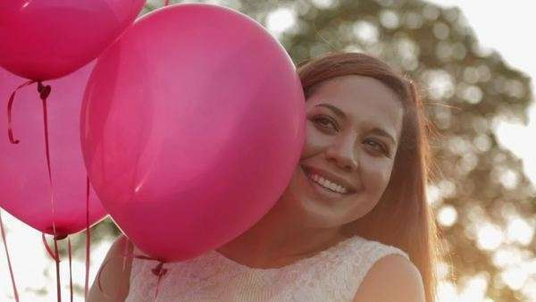 Smiling Hispanic woman holding red balloons Royalty-free stock video