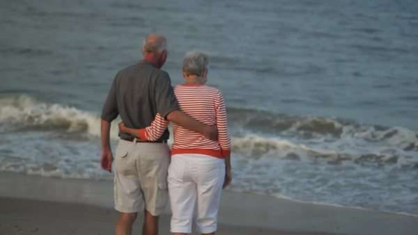 Senior Caucasian couple hugging on beach and looking at ocean Royalty-free stock video