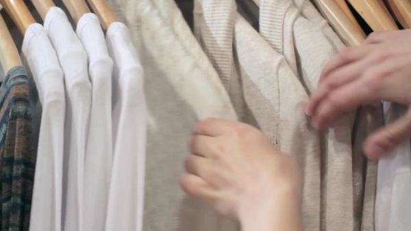 Woman's hands run across a rack of clothes, browsing in a boutique. Dolly shot from the side Royalty-free stock video