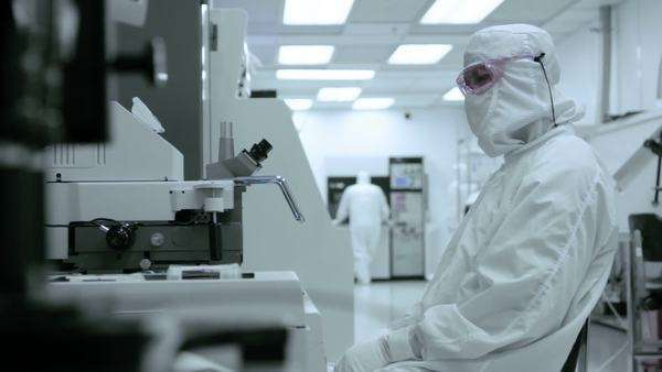 Technician checks part of the process during silicon chip manufacture in a clean room, mid shot with dolly move from left Royalty-free stock video