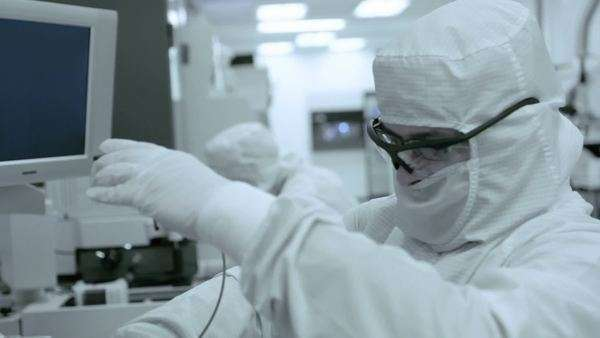 Two scientists oversee a photo-chemical part of the process during silicon chip manufacture in a clean room, medium close-up, side view Royalty-free stock video