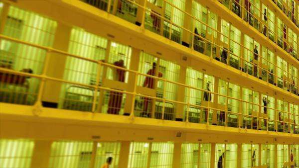 Camera moves past rows of prisoners serving time in a large cell block Royalty-free stock video
