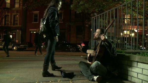 Young man playing a worn-out guitar on the night time streets of Manhattan, NY. Young woman listens Royalty-free stock video