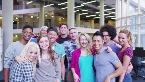 Portrait of a happy mixed ethnicity group of student friends in college library Royalty-free stock video