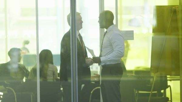 Two businessmen meet and shake hands in modern city office Royalty-free stock video
