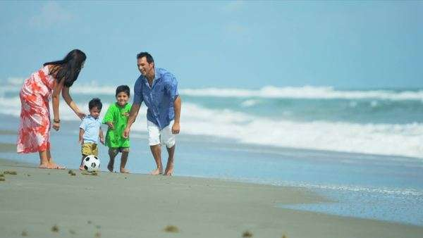 Latin American young loving parents walking on beach playing football with sons shot on RED EPIC. Royalty-free stock video