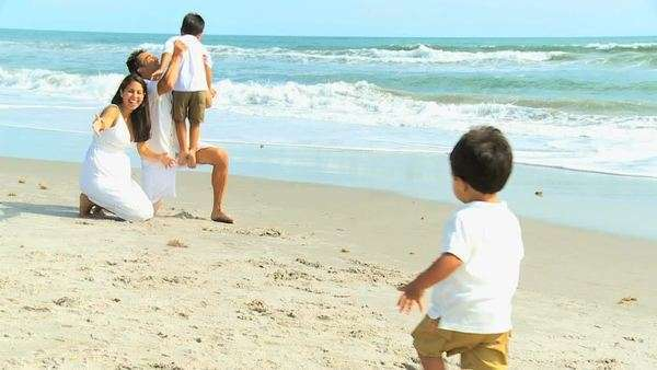 Cute little ethnic brothers playing beach with young Hispanic parents wearing casual white clothing Royalty-free stock video