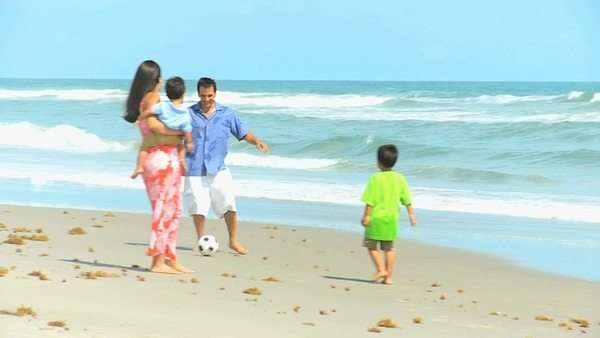 Young Hispanic parents dressed colorful casual clothes vacation playing football by ocean pre school sons. Royalty-free stock video