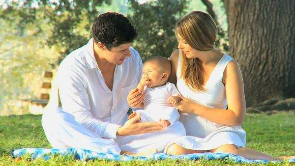 Young Caucasian parents sitting outdoors on the grass spending time with their young baby girl. Royalty-free stock video