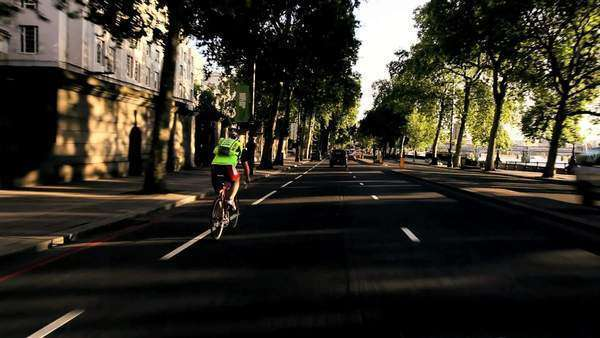 Point of view driving through city streets in early morning with commuters cycling to work. Royalty-free stock video