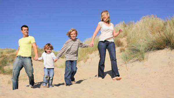 Attractive young Caucasian family enjoying vacation time together on coastal sand dunes. Royalty-free stock video