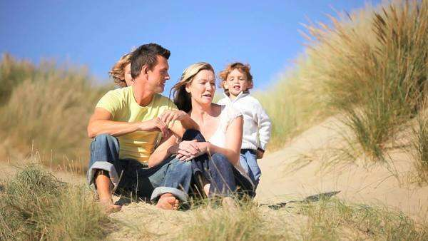Attractive young Caucasian family enjoying time together and the children having fun playing in sand dunes. Royalty-free stock video