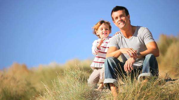 Adorable little blonde boy and his young father enjoying time together  sitting in sand dunes by the coast. Royalty-free stock video