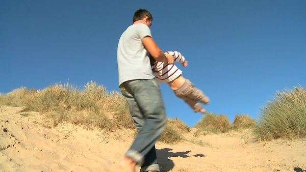 Young Caucasian father with his young son playing together in sand dunes by the coast filmed at 60FPS. Royalty-free stock video