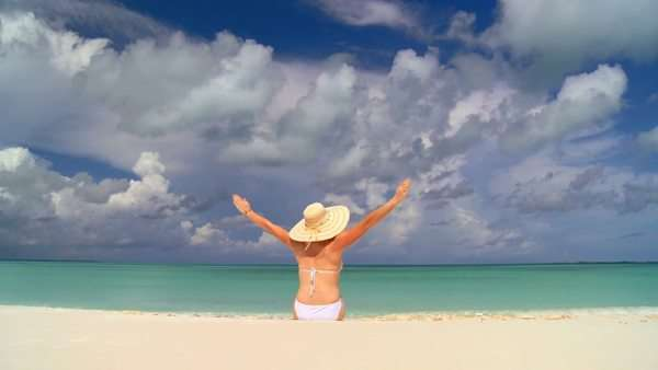 A woman in a straw hat sits on a tropical beach with her arms in the air. Royalty-free stock video