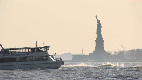 Passenger ferries pass each other in New York Harbor near the Statue of Liberty. Royalty-free stock video