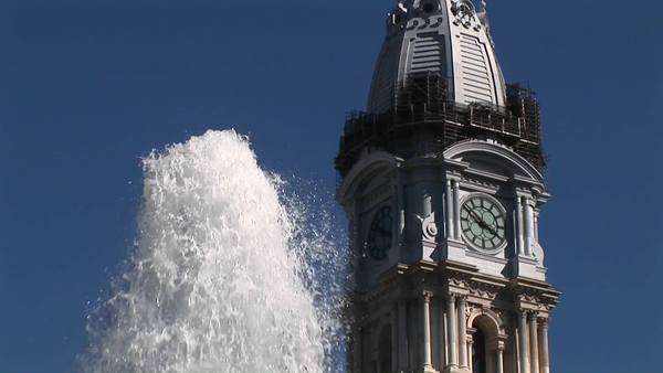 Philadelphia's ornate City Hall building towers over a fountain spraying water. Royalty-free stock video