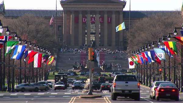 The camera pans up from the traffic and flags on Benjamin Franklin Parkway to the Philadelphia Museum of Art and its famous steps. Royalty-free stock video