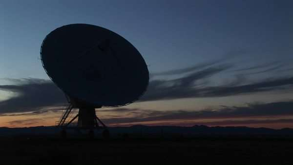 Medium-shot of a silhouette of a satellite dish in the array at the National Radio Astronomy Observatory in New Mexico Royalty-free stock video