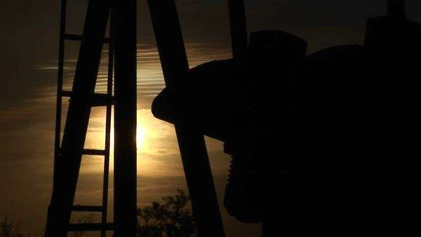 Close-up of a silhouetted oil pump turning in the New Mexico desert. Royalty-free stock video