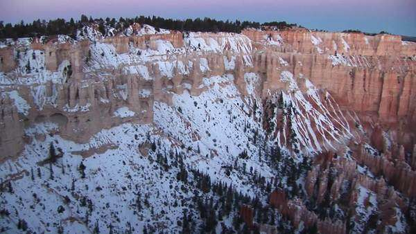 Panoramic pan-right along the snow-covered claron formations of Bryce Canyon National Park. Royalty-free stock video