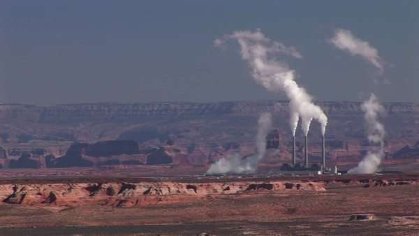 Medium-shot of a factory in the Arizona Desert disgorging pollution. Royalty-free stock video
