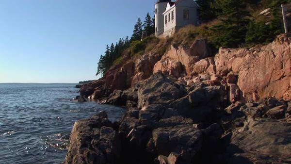 A lighthouse on the edge of a cliff overlooks the ocean. Royalty-free stock video