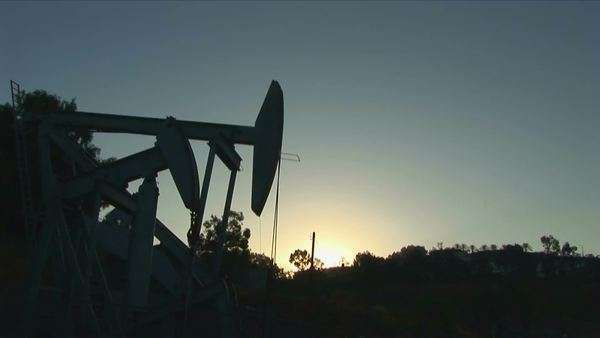 An oil well derrick is silhouetted against a glowing sky. Royalty-free stock video