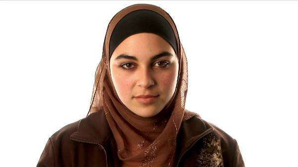 A young woman wears an Islamic hijab as she puts on her eyeglasses. Royalty-free stock video