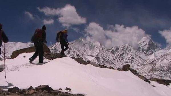 Climbers near Mt. Everest in Tibet walking over a snow hill with Mt. Pumori in the background Royalty-free stock video