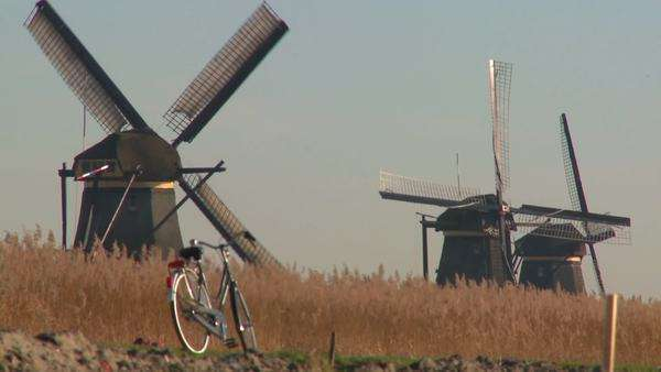 A bicycle is parked along a path in Holland with windmills in the background. Royalty-free stock video
