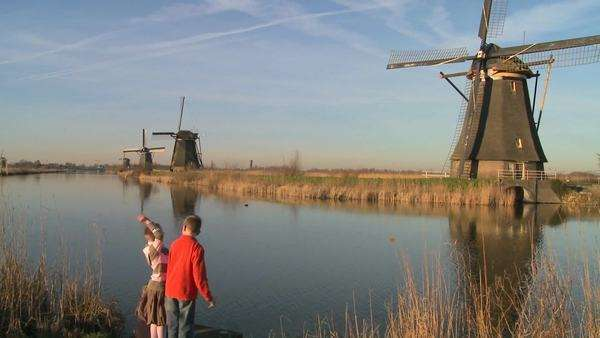 children play beside a canal and windmills in Holland. Royalty-free stock video