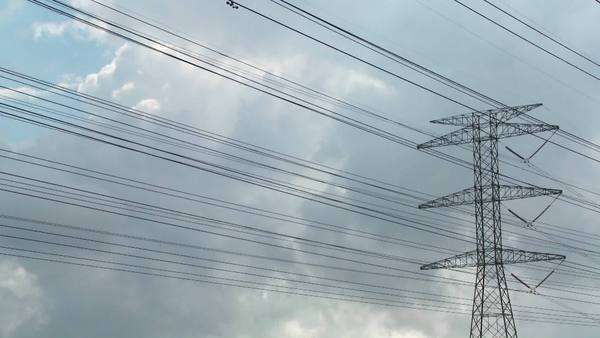 Timelapse of clouds moving behind high tension wires and power lines. Royalty-free stock video