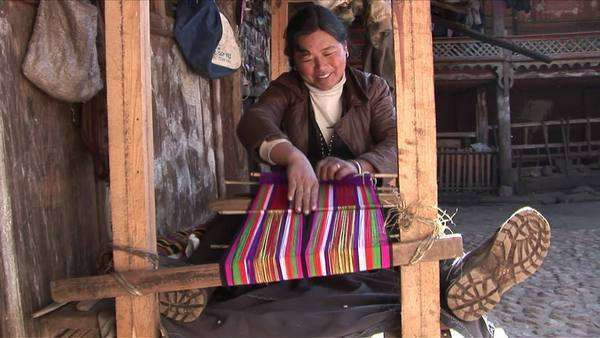 A woman operates a basic loom in a Chinese village. Royalty-free stock video
