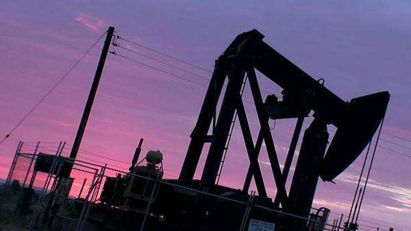 An oil derrick pumps against a purple sky. Royalty-free stock video