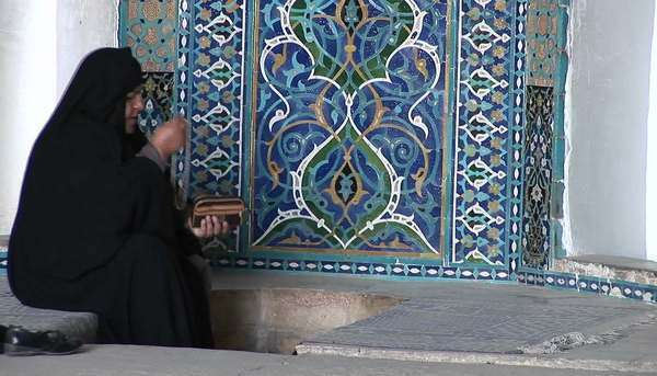 A woman wearing a chador sits before a carpet in a bazaar in Iran. Royalty-free stock video