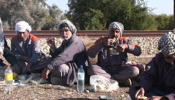 Men wearing the traditional muslim headdress, or keffiyeh, sit by a fire outside in Iran. Royalty-free stock video