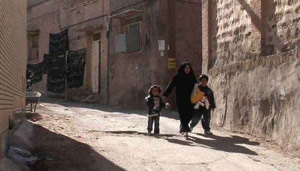 A woman wearing a chador walks with two children down an ancient alley in Iran. Royalty-free stock video