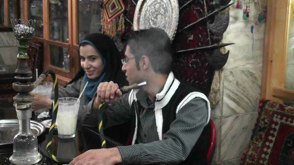 A woman wearing a headscarf and a man smoke a hookah pipe in an outdoor cafe in Iran. Royalty-free stock video