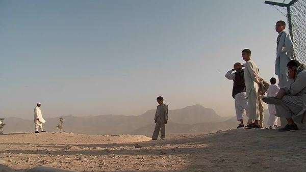 Kids chase and play with kites in an empty lot in kabul, Afghanistan. Royalty-free stock video