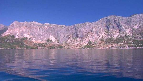 View from a sailboat motoring along a glassy ocean with mountainous crestline in the distance. Royalty-free stock video