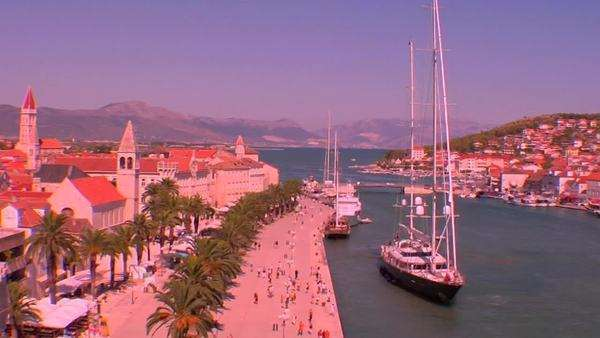 Aerial view of Trojir, Croatia's port and 1000 year old city. People walk along the port as a large yacht docks. Royalty-free stock video
